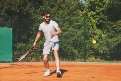 Junger Mann, der Tennis auf der öffentlichen Sitzung spielt Stockfotos