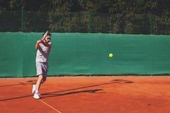 Junger Mann, der Tennis auf der öffentlichen Sitzung spielt Stockfoto