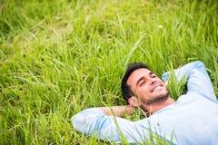 Junger Mann, der, träumend und auf dem grünen Gras sich entspannen liegt lizenzfreie stockbilder