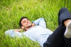 Junger Mann, der, träumend und auf dem grünen Gras sich entspannen liegt stockbilder