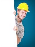 Junger Mann, der tragenden Schutzhelm der leeren Anschlagtafel hält Lizenzfreie Stockbilder