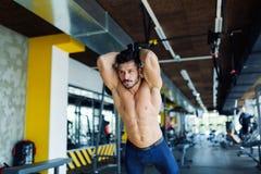 Junger Mann, der trx Übung in der Turnhalle tut Stockfotos