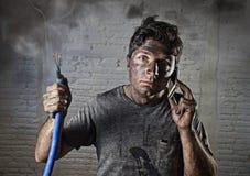 Junger Mann, der um Hilfe nach Unfall mit schmutzigem gebranntem Gesicht im lustigen traurigen Ausdruck ruft Stockfoto