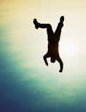 Junger Mann, der unten auf Himmelhintergrund fällt Junger Mann, der unten auf Himmelhintergrund fällt Lizenzfreies Stockfoto