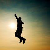 Junger Mann, der unten auf Himmelhintergrund fällt Junger Mann, der unten auf Himmelhintergrund fällt Lizenzfreies Stockbild