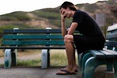 Junger Mann, der unten niedergedrückt mit seinen Händen über Gesicht sitzt Lizenzfreie Stockfotografie