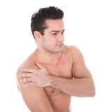 Junger Mann, der unter den Schulterschmerz leidet stockfotos