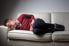 Junger Mann, der unter den schweren Bauchschmerz leidet Stockfotografie