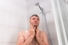 Junger Mann, der unter flüssigem Wasser in der Duschkabine steht lizenzfreies stockbild