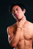 Junger Mann, der unter Nackenschmerzen leidet Stockfotos