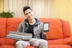 Junger Mann, der Unterschied zwischen ebook Leser zeigt stockfotografie