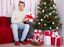 Junger Mann, der in verziertem Wohnzimmer mit Weihnachtsbaum sitzt Lizenzfreie Stockfotos
