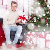 Junger Mann, der in verziertem Wohnzimmer mit Weihnachtsbaum sitzt Lizenzfreie Stockfotografie