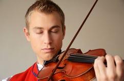 Junger Mann, der Violine spielend genießt Stockfotos