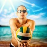 Junger Mann, der Volleyball auf dem Strand spielt Stockbilder