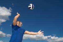 Junger Mann, der Volleyball spielt Stockbild
