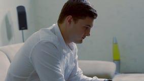 Junger Mann, der vom Haus auf einem Laptop arbeitet stock footage