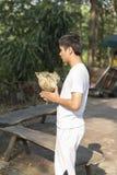 Junger Mann, der vor Klassifikationszeremonie des buddhistischen Mönchs betet Stockbilder