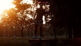 Junger Mann, der Vorwärtsrolle im Park an der Sonnenuntergangszeitlupe tut stock video footage