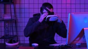 Junger Mann, der VR-Kopfhörer trägt und virtuelle Realität erfährt stockbild