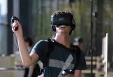 Junger Mann, der VR-Satz am Sonarfestival mit Handgriffen verwendet Lizenzfreie Stockfotos