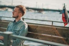 Junger Mann, der weg im Sonnenuntergang St Petersburg, Russland betrachtet Sommerlebensstilporträt im Freien des jungen bärtigen  Stockfotos