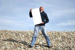 Junger Mann, der weiße Karte anhält stockfoto