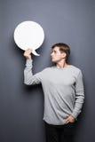 Junger Mann, der weiße leere Spracheblase mit Raum für den Text lokalisiert auf grauem Hintergrund hält Stockfotografie