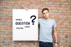 Junger Mann, der whiteboard mit Lösungsproblemen hält Lizenzfreies Stockbild