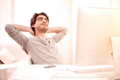 Junger Mann, der während eines Bruches im Büro sich entspannt Lizenzfreie Stockfotos