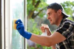 Junger Mann, der Windows säubert Fensterputzer Stockfotos