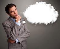 Junger Mann, der an Wolkenrede oder Gedankenblase mit Spindel denkt Stockfotografie