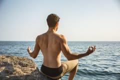 Junger Mann, der Yoga-Übung durch Meer meditiert oder tut Stockfoto