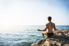Junger Mann, der Yoga-Übung durch Meer meditiert oder tut Stockfotos