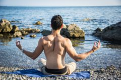 Junger Mann, der Yoga-Übung durch Meer meditiert oder tut Lizenzfreie Stockfotos