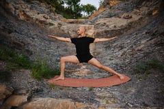 Junger Mann, der Yoga in der Kriegershaltung auf Felsen tut Stockfotos