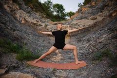 Junger Mann, der Yoga in der Kriegershaltung auf Felsen tut Lizenzfreie Stockfotografie