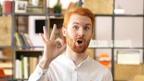 Junger Mann, der Zeichen des O.K.s, Zufriedenheit mit seinem Handzeichen zeigt Stockfoto