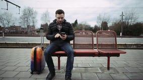 Junger Mann, der Zeit auf seiner Uhr sitzt an der Bahnstation wartet und überprüft stock footage