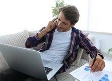 Junger Mann, der zu Hause auf einem Smartphone ein Finanzdiagramm bespricht Lizenzfreie Stockfotos