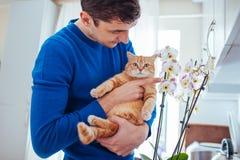 Junger Mann, der zu Hause eine Katze nahe der Orchidee h?lt stockbild