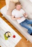 Junger Mann, der zu Hause eine Tablette verwendet Stockfotos