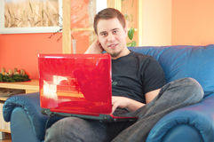 Junger Mann, der zu Hause an Laptop-Computer arbeitet lizenzfreie stockfotografie