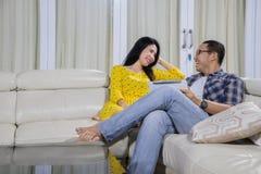 Junger Mann, der zu Hause mit seiner Frau spricht Stockfoto
