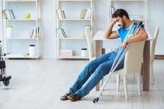 Junger Mann, der zu Hause nach Chirurgie mit Krücken und einem w wieder herstellt Lizenzfreie Stockbilder