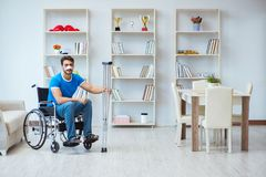 Junger Mann, der zu Hause nach Chirurgie mit Krücken und einem w wieder herstellt Lizenzfreies Stockfoto
