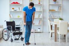 Junger Mann, der zu Hause nach Chirurgie mit Krücken und einem w wieder herstellt Stockfoto