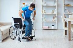 Junger Mann, der zu Hause nach Chirurgie mit Krücken und einem w wieder herstellt Stockfotografie