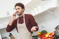Junger Mann, der zu Hause romantischen Telefonanruf des Abendessens kocht stockfotografie