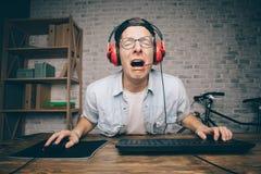 Junger Mann, der zu Hause Spiel spielt und playthrough oder Durchlaufvideo strömt Lizenzfreie Stockbilder